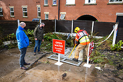 © Licensed to London News Pictures. 06/10/2020. Bury, UK. Firefighters unblock a culvert . Houses and roads flood on Tottington Road in Bury after drainage systems are overwhelmed by the volume of water and blockages in the wake of persistent, heavy rain . Photo credit: Joel Goodman/LNP