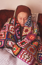 Elderly woman sitting at home wrapped in blankets and woollen hat,