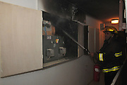 A fire broke out in a household electrical fuse box flames consumed the board. Fireman extinguishes the flames. Photographed in Israel