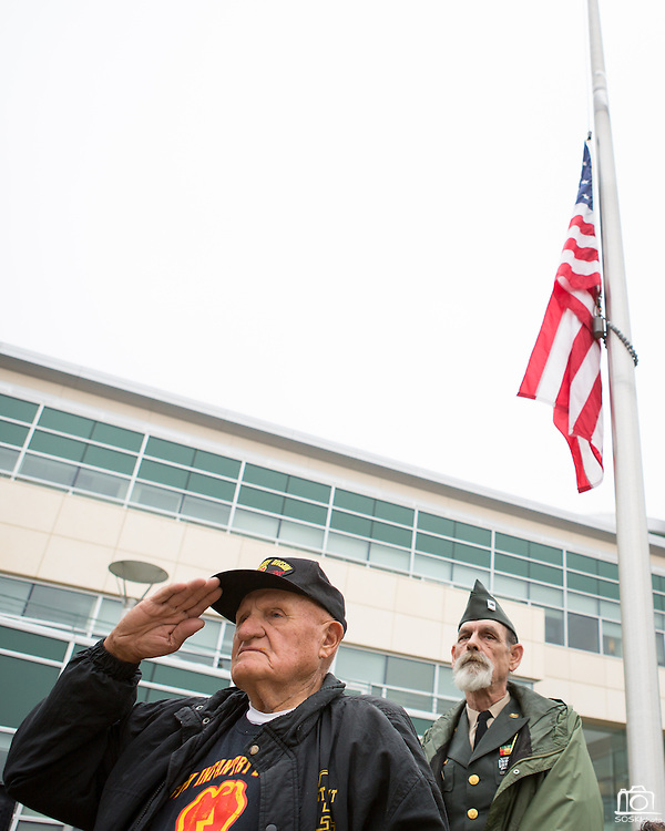 """Ed Hart, United States Army veteran of the Korean War (1953-1954), foreground, and Kraig Bunnell, United States Army veteran of the Vietnam War, salute during the playing of """"Armed Forces Salute"""" during the Milpitas Memorial Day Ceremony at Veterans Memorial Flag Plaza in Milpitas, California, on May 27, 2013. (Stan Olszewski/SOSKIphoto)"""