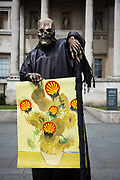 'Death', a street performer outside the Natinla Gallery holds a Van Gogh picture defaced with Shell logos in sympathy with the recent protest at the gallery. Environmental political activists stage an performance at the national Gallery to protest against Shell's sponsorship of the gallery and the privatisation of the gallery staff.