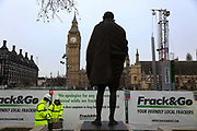 Greenpeace pretends to frack with their own mock fracking company Frack&Go and drilling rig in Parliament Square, Central London, 9th February 2016.  The Statue of Mahatma Gandhi watches over the Greenepeace fracking site.  Greenpeace wants to highlight that fracking is a highly polluting and destructive way of extracting gas and to push for increased awareness of this, they set up their own rig outside Parliament without prior permission.