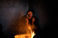A man from Afghanistan is seen smoking a sigarette next to a bonfire in an abandoned squat. A group of more than a hundred are living in an abandoned factory in Bihac waiting to try 'the game', as migrants call their attempts to cross the Bosnian Croatian border. January 25, 2021.