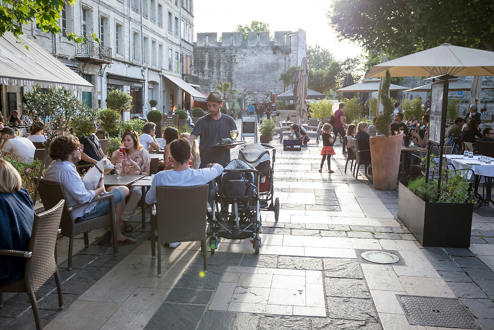 People enjoy an early summer evening at outdoor cafes in Place Crillon in Avignon, France. At one table, a dog is sitting in a man's lap and a baby is reaching for a beer.