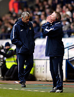 Photo: Jed Wee.<br />Bolton Wanderers v West Ham United. The Barclays Premiership. 11/03/2006.<br /><br />West Ham's disconsolate manager Alan Pardew (L) hangs his head as Bolton coach Sammy Lee continues to urge his team forward.