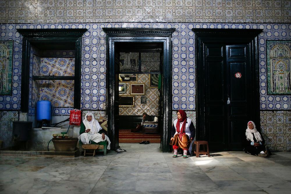 "The temple of patron saint Sidi Mehrez in the center of Tunis is guarded, maintained and visited by women. 79 year-old Khira (left), who has been guarding the temple for 50 years, gives holy water to a faithful. The well in the mausoleum is blessed. to complete the ""ziara"" (the visit), the faithfuls have to drink its water. On the right, next to the door, is Zora. The mausoleum is protected by the police. Since the fall of Ben Ali's regime in 2011, attacks against mausoleums and Sufi places of worship by radical Islamists are frequent. Islamists consider prayers to saints a sin because it associates other gods or beings with Allah. Since 2011, 80 mausoleums, mainly guarded by women, have been attacked. <br /> <br /> Le temple de Sidi Mehrez à Tunis. A gauche, Khira, 79 ans, gardienne du temple de Sidi Mehrez depuis 50 ans. A droite de la porte : Zora.  Le mausolé est protégé par la police : depuis la chute de Ben Ali en 2011 les attaques contre les mausolées et les lieux de culte des confréries soufies, très nombreux en Tunisie, sont l'œuvre de l'islam rigoriste: la prière des saints est une hérésie à leurs yeux. Depuis 2011, 80  Mausolée - le plus souvent tenus par des femmes - ont été  attaqués en Tunisie."