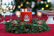 Burning Red soy candle created by Bridge NIne  Candle sitting on small table wreath with wine glasses and Christmas Tree in the background