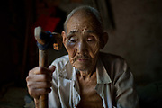 87 year old Dou Shengli sits in his home at a rural village near Fuyang, Anhui Province,  China on 28 August  2013.  As able-bodied adults seek work in cities in hopes of better income, more and more villages in China are inhabited mostly by the elderly and children.