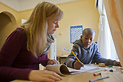 A young school-boy doing a writing exercise with a volunteer teacher in a class room in Zonnebloem School, Cape Town, South Africa.  The volunteer teacher has been provided to the school by Shine Centre which is a charity that aims to address the high illiteracy rate in South Africa by improving literacy levels among children in schools and disadvantaged communities.