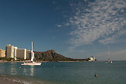 A catamaran sets sail from Waikiki Beach with Diamond Head Crater in the background.