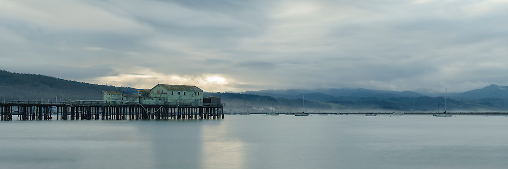 Sunrise over pier and storm clouds near Pillar Point Harbor, Half Moon Bay, California