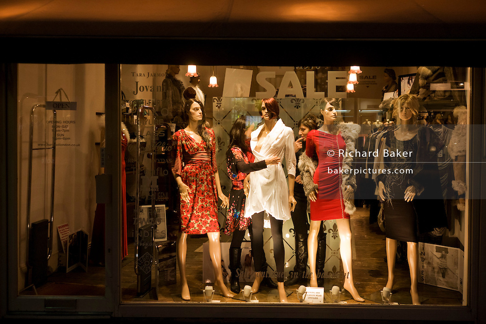 Window dressers adjust womens' clothes worn by shop window mannequins on Chelsea's Kings Road.