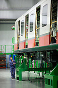 Workers operate to assemble a subway car at the China South Locomotive & Rolling Stock Corp. Ltd. and Siemens AG's joint venture Rail Transit Equipment Base in Guangzhou, Guangdong Province, China, on November 13, 2011. At least 15 cities in China are building subway lines and 36 more have submitted plans, causing concerns that local debt levels will become unmanageable in the future.