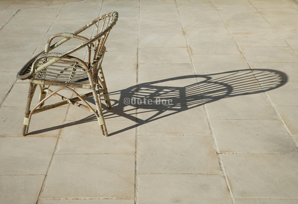a single outdoor wicker chair with a large shadow