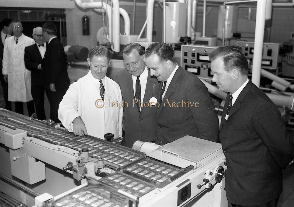 8/9/1964<br /> 9/8/1964<br /> 8 September 1964<br /> <br /> Mr. Arthur Behan the Assistant Managing Director at Urney Choclates, Mr J. Walsh of the Irish Press, Mr. Padraig O'Hannraghan Director of the Goverment Information Bureau and Mr C. Howard from the Dept. of External Affaires look at the product traveling on the assembly line.
