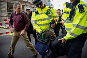 Paraolympian James Brown looks on as police officers arrect journalist George Monbiot on Whitehall on 16th October 2019 in England, United Kingdom.  Extinction Rebellion climate activists sit down in the road despite the police imposing a section 14 of the Public Order Act 1986  in effect banning all protest by the group in London.