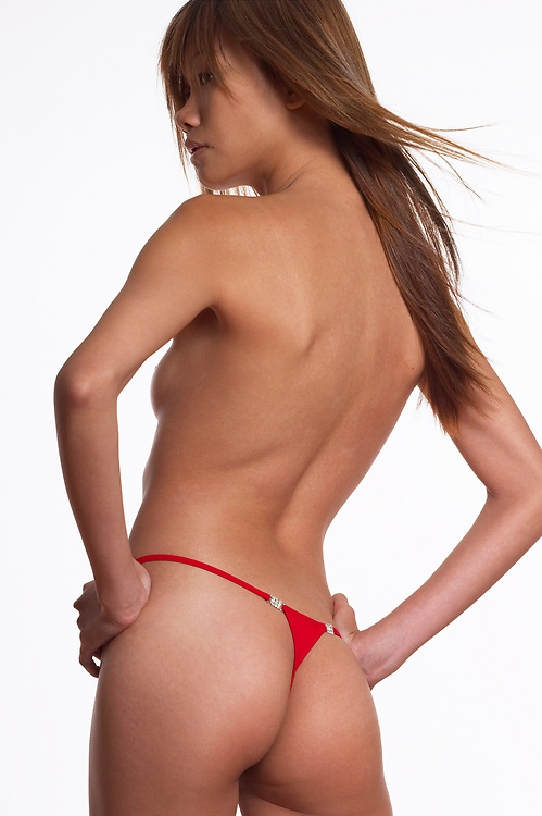 Rear view of nude woman wearing red thong, hair blowing and against a white background