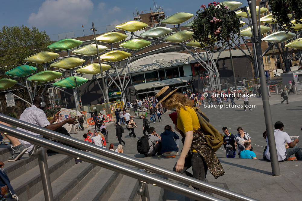 Londoners use the precinct space at Stratford's train station with the Olympic kinetic Shoal artwork, installed at the older Stratford Centre opposite.