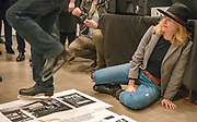 """Portland, Oregon, USA. 26 FEB, 2018. The photographer Leah Nash avoids the blades of an ice skating performance artist as he shreds  photographer Robert Frank's work at Blue Sky Gallery in Portland, Oregon, USA. The work was destroyed in a """"Destruction Dance"""" performance defacing the photographs with ink and mutilation with scissors, knives and even ice skates  at the end of it's run. The destruction was Frank's protest regarding today's greed in the global art market."""
