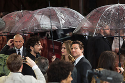 "© Licensed to London News Pictures. 28/05/2014. London, UK. Tom Cruise and Emily Blunt shelter from heavy rain under giant umbrellas this morning at the UK premiere of the ""Edge of Tomorrow"" at the BFI IMAX in London. Photo credit : Vickie Flores/LNP"