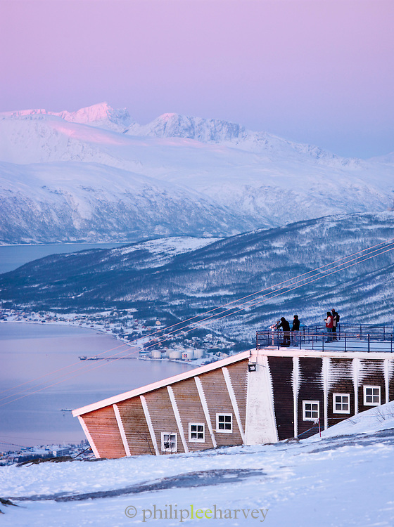 Tourists look at a view of Tromso from the top of Mount Storsteinen, reached by cable car, at Tromso, Norway
