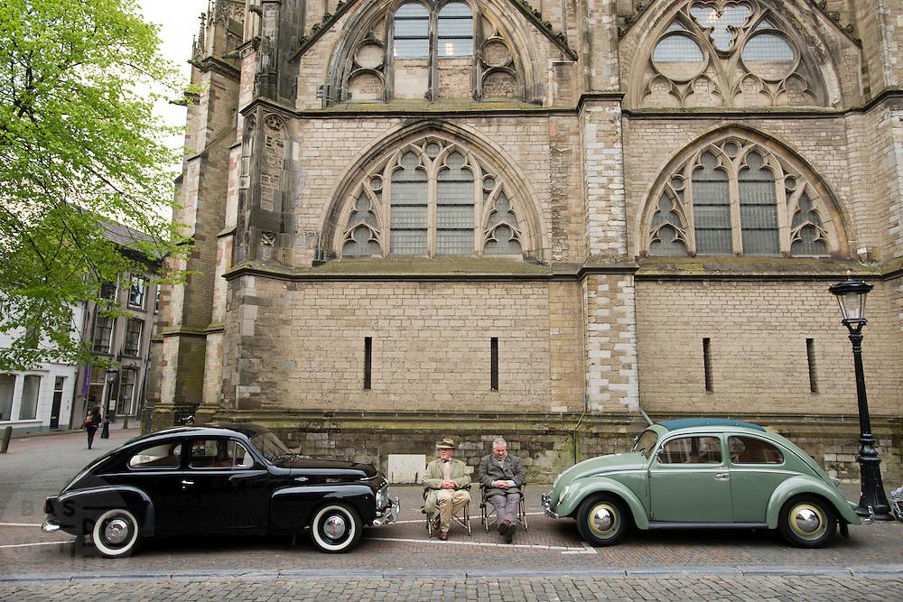 Twee acteurs zitten tussen twee oldtimers bij een filmset in Utrecht.<br /> <br /> Two actors are waiting between two old-timers at a filmset in Utrecht.
