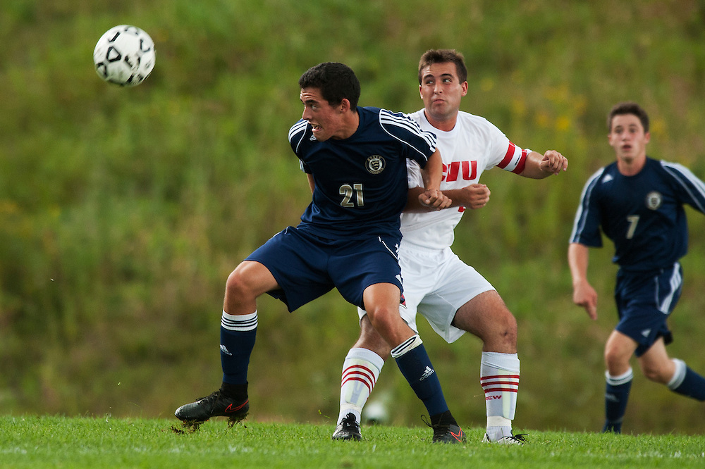 Essex's Noah Ferris (21) gets past CVU's Will Yakibuk (21) to play the ball during the boys varsity soccer game between the Essex Hornets and the Champlain Valley Union Redhawks at CVU High School on Wednesday afternoon September 9, 2015 in Hinesburg. (BRIAN JENKINS/for the FREE PRESS)