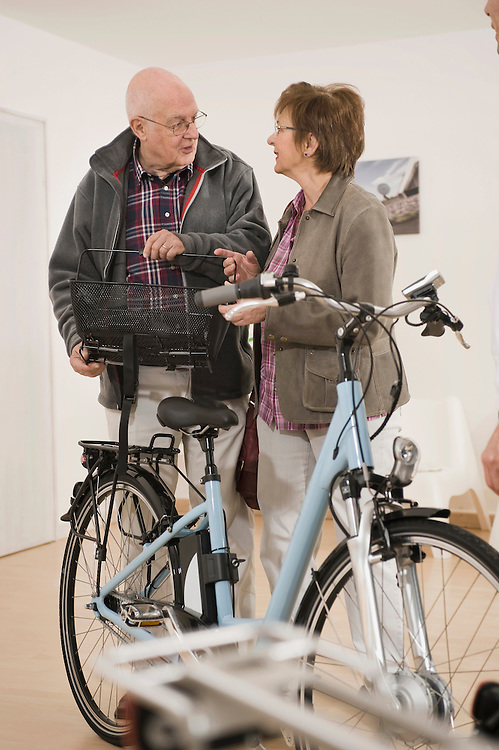 Senior man and woman with electric bicycle