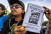 """25 MAY 2014 - BANGKOK, THAILAND:  A Thai man carries a """"wanted"""" poster with a picture of Gen. Prayuth Chan-ocha, leader of the coup that unseated the elected civilian government. Public opposition to the military coup in Thailand grew Sunday with thousands of protestors gathering at locations throughout Bangkok to call for a return of civilian rule and end to the military junta.    PHOTO BY JACK KURTZ"""