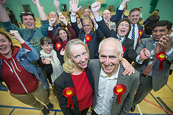 © Licensed to London News Pictures . 10/10/2014 . Heywood , UK . Labour candidate Liz McInnes (front left) with her partner Steve Duxbury , cheered by her team behind , after Labour's victory is declared. The count at the Heywood and Middleton by-election , following the death of sitting MP Jim Dobbin . Photo credit : Joel Goodman/LNP