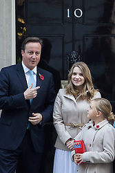 © licensed to London News Pictures. London, UK 29/10/2013. Prime minister David Cameron buying a poppy from The Poppy Girls outside No.10 in Downing Street to support the Poppy Appeal on Tuesday, 29 October 2013. Photo credit: Tolga Akmen/LNP