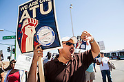 "10 MARCH 2012 - PHOENIX, AZ:      RICARDO RODRIGUEZ, a bus driver for more than 12 years in Phoenix, shouts a strike breaking ""scab"" driver during a picket in Phoenix Saturday. More than 600 Phoenix bus drivers, employed by Veola Transportation Services, are on strike after negotiations broke down. Drivers from Amalgamated Transit Union Local 1433 have been negotiating for more than two years with Veola. The dispute centers around wage and benefits like sick leave accrual, retirement benefits, and health care coverage. Drivers started walking their picket line early Saturday morning.  PHOTO BY JACK KURTZ"