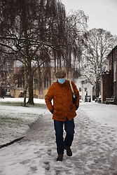 Man wearing face mask during Coronavirus lockdown 3, walking through Cathedral Close in the snow, Norwich UK January 2021. Posed by model