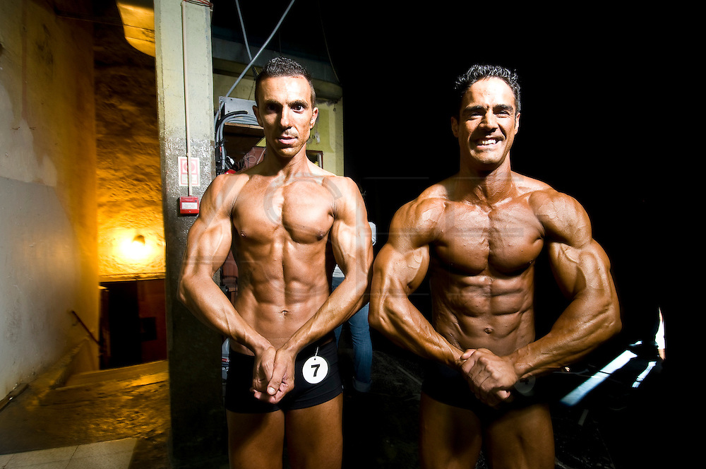 For two years in a row, in a rundown theater in Porto, the Portuguese National Championship of Bodybuilding WABBA happened. Several athletes, from allover the country came to this one day competition. <br /> These are photos from the backstage, where the athletes exercise and get body paint for the stage presentation. The muscles and the gold and brown colors get ready in the confusion of tubes, abandoned wood from different theater plays, photos from the past and dressing rooms with 100 years old. <br /> Pedro cerdeira and Ruizinho ( Rui Pereira) national champions of fitness.