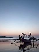 Fishermen bringing thier boat onto the beach, Bali, Indonesia.