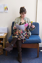 Patient sitting in dentist waiting room; reading a magazine,