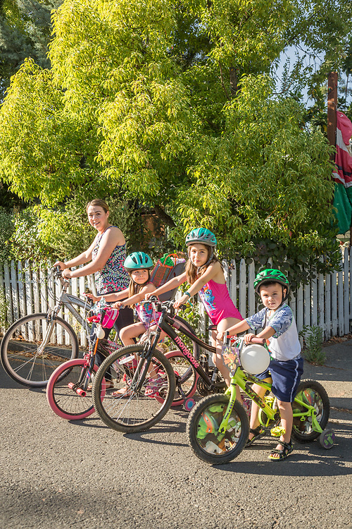 """""""We lived in Santa Rosa and had to get in the car to go anywhere.  Now that we live in Calistoga, we ride our bikes everywhere.""""  -Special Ed Para instructor Melinda Mendoza with her kids: Nataly, Emily, and Anthony, in front of their home on Grant Street in Calistoga."""
