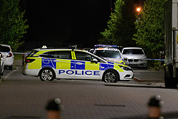 © Licensed to London News Pictures. 15/08/2021. Slough, UK. Police vehicles maintain a scene cordon following a double stabbing in Cippenham, Slough. Emergency services were called at approximately 17:00BST on Sunday 15/08/2021 to the Eltham Avenue area of Slough to reports that two male teenagers had been assaulted during an altercation between a number of youths. Both were taken to hospital with stab wounds. Photo credit: Peter Manning/LNP