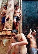 """V. 12. Valencia, 31/08/2005. Unos jovenes luchan con tomate en la puerta de la iglesia durante la fiesta de la """"tomatina"""" de Buñol, Valencia, en la que cerca de 40.000 personas se han lanzardo durante una hora 120 toneladas de tomates maduros, una tradición que cuenta ya con 60 años de antigüedad. EFE/Kai Försterling."""