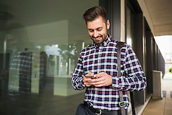 Young man text messaging on mobile phone and smiling, Munich, Bavaria, Germany
