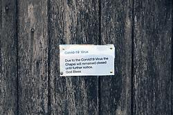 Covid 19 - Chapel closed due to Coronavirus. The sign ends God Bless', St Aldhelm's Head Dorset April 2020