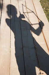 Shadow of person on wood holding folding ruler