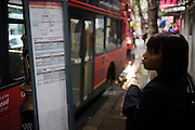A young woman commuter reads a bus destination timetable sign at a flooded bus stop.