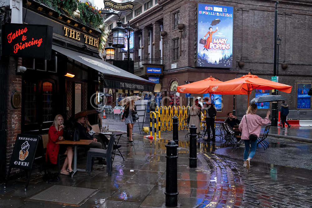 On a rainy night in Soho, Londoners cross a pedestrianised Old Compton Street at a time when recently re-opened bars and restaurants are desperate for customer business during the coronavirus pandemic, on 27th August 2020, in London, England.
