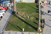 Activity around the marina waterfront area with a woman walking on a tightrope set between two trees and passersby watching, Faro, Algarve, Portugal, Europe