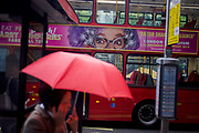 "The Australian character Dame Edna Everage looks over the street from a bus ad to a woman carrying an umbrella during autumnal London showers. In autumnal shower, the capital is dark apart from the bright colour of the brolly and the advertising banner across the side of the double-decker bus. Dame Edna is a character created and performed by Australian dadaist performer and comedian Barry Humphries, famous for her lilac-coloured or ""wisteria hue"" hair and cat eye glasses or ""face furniture,"" her favourite flower, the gladiolus (""gladdies"") and her boisterous greeting: ""Hello, Possums!"""