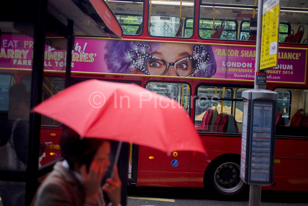 """The Australian character Dame Edna Everage looks over the street from a bus ad to a woman carrying an umbrella during autumnal London showers. In autumnal shower, the capital is dark apart from the bright colour of the brolly and the advertising banner across the side of the double-decker bus. Dame Edna is a character created and performed by Australian dadaist performer and comedian Barry Humphries, famous for her lilac-coloured or """"wisteria hue"""" hair and cat eye glasses or """"face furniture,"""" her favourite flower, the gladiolus (""""gladdies"""") and her boisterous greeting: """"Hello, Possums!"""""""