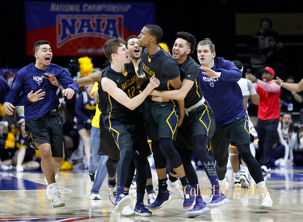 Graceland's Justin Harley, center, celebrates his game-winning overtime basket with Dalton Payton, left, and Waseem Limbada, right, and other teammates in the NAIA championship men's college basketball game, Tuesday, March 20, 2018, in Kansas City, Mo. Graceland beat LSU Alexandria 83-80. (AP Photo/Colin E. Braley)