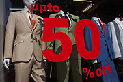 The fashionable styles of menswear suits worn by shop mannequins and discounted by 50% in the window of an Oxford Street window, on 24th August 2016, in London, UK. The trend at the moment is for slim-fitting suits with a shine giving them a 1960s retro look work by young millennial men in Britain.