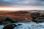 First light adds a touch of warmth to a distant Over Owler Tor, viewed from a frosty Higger Tor. Peak District.